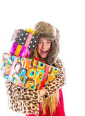 Blond winter kid girl with stacked presents smiling — Stock Photo