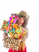 Blond winter kid girl with stacked presents smiling — Stockfoto