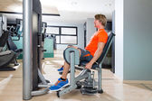 Hip abduction blond man exercise at gym indoor — Stock Photo