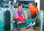 Gym leg extension workout woman personal trainer — Stock Photo
