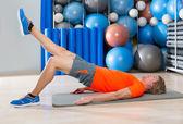 Bacak uzatma sarışın adam spor salonunda egzersiz ile kalça kaldırma — Stok fotoğraf