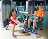 Gimnasio leg curl máquina ejercicio Rubio hombre sentado — Foto de Stock