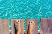 Sandy feet on the pier tropical turquoise sea — Stock Photo