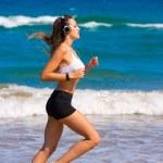 Brunette girl running on the beach headphones — Stock Photo #70622251