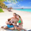 Blond tourist couple playing guitar at beach — Stock Photo #70624665