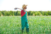 Farmer man with hoe looking at his field — ストック写真