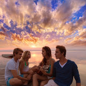 Friends group at sunset beach having fun with guitar — Stock Photo