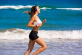 Brunette girl running on the beach headphones — Stock Photo