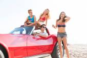 Friends group at beach in sports car convertible — Stock Photo
