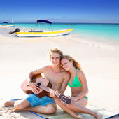Blond tourist couple playing guitar at beach — Stockfoto