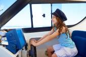 Kid girl pretending be a captain sailor cap in boat — Stock Photo