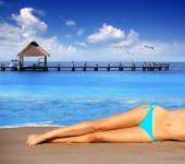 Bikini girl legs lying on beach sand in summer — Stock Photo