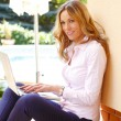 Mature woman sitting with laptop — Stock Photo #70709849