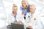 Doctors and nurses with laptop — Stock Photo