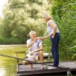 Senior couple relaxing and fishing — Stock Photo #77833288