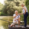 Senior couple relaxing and fishing — Stock Photo #77833338