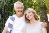 Happy senior couple sitting at the lakeside — Stock Photo