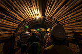 Eerie mining tunnel with tourists. — Stock Photo