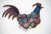 Cute iron rooster with porcelain dishes. — Стоковое фото