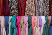 Many stylish scarfs for sale in a store — Stock Photo