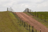 Hill with a fence and dirt road in Alentejo — Stock Photo