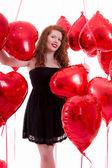Niña feliz entre globos rojos — Foto de Stock