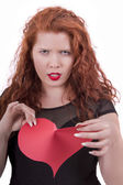 Angry young girl tearing a red heart — Stock Photo