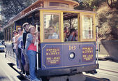 Passengers riding cable car in San Francisco — ストック写真