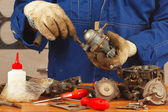 Serviceman repairing parts of the car engine in workshop — Stock Photo