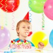 Little boy in festive hat with birthday cake with whistle and holiday balloons — Stock Photo #54202211