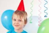 Little blonde boy in festive cap with holiday balls and streamer — Stock Photo