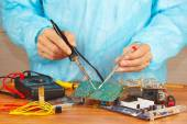 Serviceman solder electronic board of device in service workshop — Stock Photo