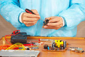 Serviceman parses electronic hardware for repair in service workshop — 图库照片