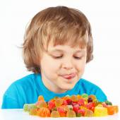 Little child looking at colored jelly candies on white background — Stock Photo