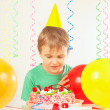Little blonde boy in holiday hat looking at birthday cake — Stock Photo #54658537