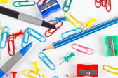 Pencil, pen, paperclips, sharpeners and thumbtacks on white desktop — Stock Photo