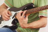 Musician put fingers for chords on electric guitar close up — Stock Photo