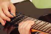 Artist put fingers for chords on electric guitar close up — Stock Photo