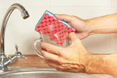Hands with sponge and dirty cup over the sink in kitchen — 图库照片