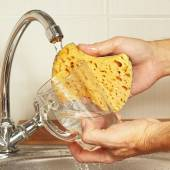 Hands wash the glass under running water in kitchen — Stock Photo