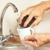 Hands with sponge wash the cup under running water in kitchen — Photo