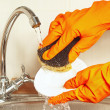 Hands in rubber gloves with sponge wash plate under running water — Stock Photo #58710873