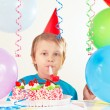 Little cute boy in holiday hat with birthday cake with whistle and festive balloons — Stock Photo #58711211