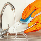 Hands in rubber gloves wash the dirty dishes under running water in kitchen — Stock Photo