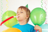 Little boy in festive hat with whistle and holiday balloons and streamer — Stock Photo