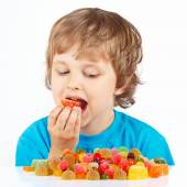 Little boy eating jelly candies on white background — Stock Photo