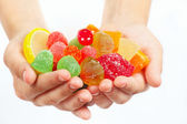 Child hands with colorful sweetmeats and jelly close up — Stock Photo
