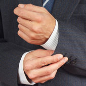 Man fastened the buttons on sleeve business suit closeup — Stock Photo