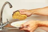 Hands with dirty dishes over the sink in kitchen — Stock Photo