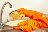 Hands in gloves with sponge and dirty saucer over the sink in kitchen — Stock Photo